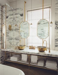 Marble bathroom with brass hardware: suspended octagon mirrors, bowl sinks