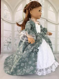 Marie Antoinette dress has lace across bodice top, around the neck, and down each side of the bodice inset. Inset and underskirt is lace over white cotton fabric and has gathered lace around the bottom. The overskirt, sleeves and bodice are made of a soft cotton. Dress is fully lined