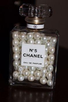 BUENA IDEA...usar frascos de perfumes finos como objetos decorativos, rellenandolos, como en este caso, con bolitas tipo perlitas...