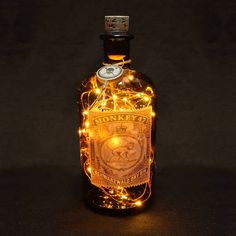 This LED bottle lamp has been made by upcycling a Monkey 47 Gin bottle. This is a 500ml / 50cl bottle fitted with warm white LEDs. The Monkey 47 Gin bottle is a fantastic, distinctive looking bottle featuring a unique cork with a metal branded band around. Protective rubber is fitted inside the drilled hole to prevent the LED lights wire rubbing and wearing on the glass. The battery unit is fitted with a 3 way switch. Switch Positions: 1. Off 2. On Power Supply: 3 x AA Batteries (N...