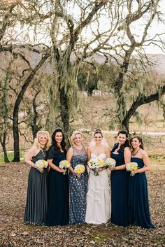 Mismatched bridesmaids are lovely. Photography: Ken Kienow  - www.kenkienow.com  Read More: http://www.stylemepretty.com/california-weddings/2014/05/27/romantic-yellow-navy-blue-wedding-at-spanish-oaks-ranch/