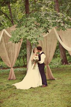 Burlap and tulle draping for an outdoor wedding...this would be very pretty adding lights and a bow for color... by jodi