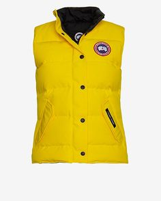 Canada Goose Freestyle Vest: Yellow: Pursuit your active lifestyle with ease. This lightweight puffer vest is water-resistant. Stand collar, logo patch at left chest, snap-placket/zip front, envelope snap pockets, and inner adhesive pocket at chest. In muted yellow. Fabric: 85% ...