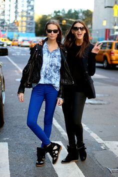 Models Mina Cvetkovic and Georgina Stojilikovic off-duty. Amazing street wear, stunning simplicity. Take notes: Casual can be chic, too! Just check out the all-black look (and sneaker wedges) on Stojilikovic that next-levels leggings and a sweater.  Cvetkovic also gets into her comfy kicks, pairing them with bright blue skinnies and a chambray shirt — smirk to match, of course. We're loving this duo of looks for blustery days like today.