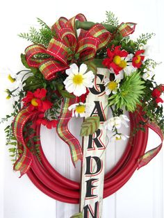 """Here we have the infamous """"Garden Hose Wreath"""" this fun and ever so popular design for your Spring and Summer decorating really has that wow factor! Did you know the Garden hose is not just for watering your garden any more? This stunning design features a pretty Red Garden Hose adorned with a Wood """"GARDEN"""" Sign that actually has a handle from a shovel at the top and a Rusty Old Faucet with a Bucket hanging from it at the bottom that really looks as though you had it in your garden for…"""