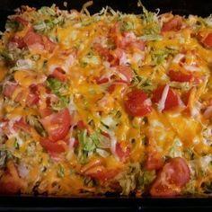 Taco Casserole:  1 7oz. bag Nacho Cheese Doritos, crushed  1 lb. hamburger, browned  1 pkg. taco seasoning, mixed according to directions  1 (8 oz.) pkg. shredded Cheddar cheese  1 (8 oz.) pkg. shredded Mozzarella cheese  Shredded Lettuce  Sliced tomato