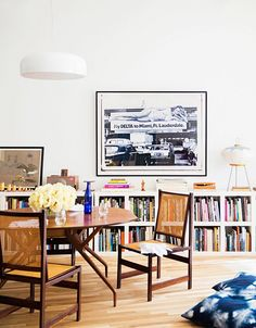 Dinning space with vintage wood chairs, book shelves, and eclectic art