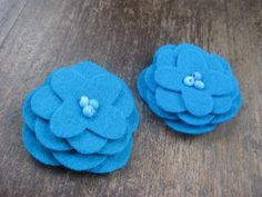 could cut out flowers like this and then sew a button in the middle