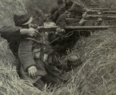 A French soldier fires over the body of a dead comrade, 1914.
