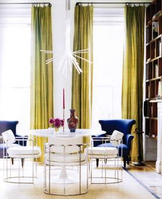 White room with pops of color. Absolutely love the tall drapes