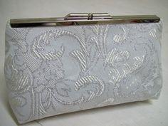 Bolsa+em+tecido+adamascado+branco+e+prata.+Forrada+com+cetim+de+seda+perola,+acabamentos+em+costura+francesa.+Fecho+em+metal+cor+prata.+Acompanha+alca+retratil+em+corrente+prateada. R$ 75,00