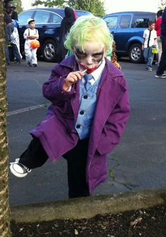 A child dressed The Joker for Halloween, specifically the Joker in The Dark Knight (played by Heath Ledger). The innocence of this child, if present, is completely masked by his costume. The scary face paint, hair paint, and trench coat resembles a truly horrifying halloween costume for a child to wear. This picture displays a rebellious child in a marvellous (by yet scary) Halloween Costume.