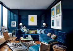 Apartment Therapy: dark blue painted walls. I'm particularly drawn to the zebra rug on the warm floor and they way it plays off the blue wall and blue sofa color.