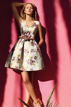 Vestido de fiesta corto escote en V y falda con volumen realizado en brocado, detalle floral en la cintura.Colección 2017 Maria Lago.