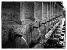 """Granfonte, Leonfonte. La Granfonte, simbolo del paese, è una delle più straodinarie fontane monumentali in stile barocco. La sua costruzione risale al 1651 su commissione della famiglia Branciforti ed oggi rappresenta il simbolo stesso di Leonforte. Essa è caratterizzata da una suggestiva sequenza di 22 arcate e 24 cannelle d'acqua, tanto che anche chiamata dagli abitanti del luogo come """"ventiquattru cannola""""."""