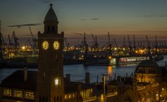 https://flic.kr/p/r8Uo9T   Landungsbrücken Tower at dusk   en: Landungsbrücken, also referred to as the St. Pauli Piers, St. Pauli Landing Stages or St. Pauli Landing Bridges, are the largest landing place in the Port of Hamburg and also a major tourist attraction.  The piers are located in the St. Pauli area of Hamburg, Germany, between the lower harbour and the Fischmarkt (Fish Market), on the banks of the Elbe river. The Landungsbrücken today form a central transportation hub, with…