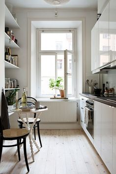 Cottage Kitchen with Drop-In Sink, Flush, Ikea Akurum Cabinets In Abstrakt High Gloss White, Hardwood floors, One-wall