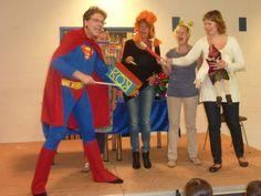Meesters en juffen helpen Supernoud met een goocheltuc door met een goochelstok over een goochelkist te zwaaien.