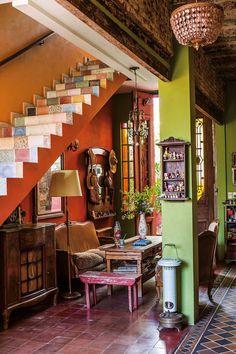 Hall de entrada colorido en tonos naranja con muebles de madera vintage. En la casa de la fileteadora Silvia Dotta.