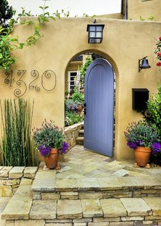 Stacked stone steps lead to a charming, arched front door that gains entrance to this Mediterranean-inspired home's fairy tale-esque courtyard. Whimsical house numbers and lush, casual plantings add to the home's rustic and welcoming vibe.