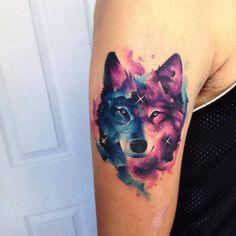 Tatuaje de un lobo de estilo acuarela situado en el brazo...