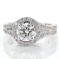 This modern diamond engagement ring has sleek lines and the micro pave in the halo and band sparkles like stars. The band is a split shank leading into the round halo. Design 1988 from Knox Jewelers