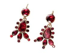 Almandine garnets with that characteristic flat cut table and minimal faceting just around the edge were ubiquitous to Georgian era jewelry and a favorite of the ladies of the period. Typically set foiled and closed back, this technique gave the gems a stunningly lush and lavish purplish color ranging from deep mulberry to claret red.    This pair of drop earrings of 9k yellow gold features what appears to be a marriage between a top round cut garnet set in a pinched collet of gold and a…