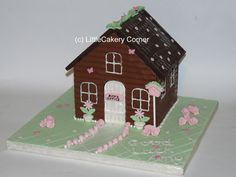 "A beautiful chocolate house in vintage style for anyone who loves the Cath Kidston genre. Pastel shades of pink, mint green and white make this a lovely feminine alternative to a cake. There are tiny handmade baby pink sweet roses, rose buds, daisies in plant pots, butterflies and a bird house. This was made as a Good Luck gift for a lady leaving to start a new job. Hence the house has an ""office"" sign on the front door. It is topped with leaves and blossoms."