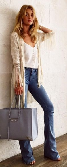 Who made  Rosie Huntington-Whiteley's white tank top, tan fringe jacket, blue tote handbag, blue flared jeans, and jewelry?