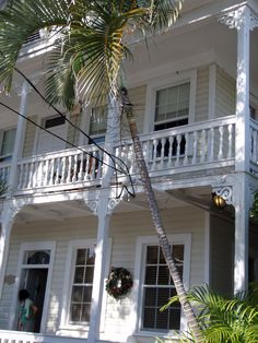 Conch pick house with porches on 2 stories adorned with white gingerbread trim