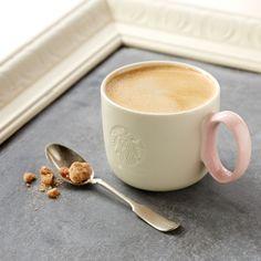 Ein Hochglanz-Kaffeebecher aus Keramik mit einem ovalen Griff in Pink.