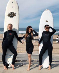A imagem pode conter: 3 pessoas, pessoas em pé, oceano, céu, sapatos, atividades ao ar livre e água