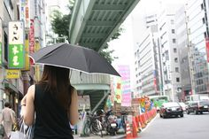 Many young, and not so young, Japanese women like to avoide ultra violet radiation and use umbrellas to shield themselves from the sun.The day on which this photograph was taken was cloudy but bright.