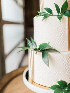 white cake with greenery leaves