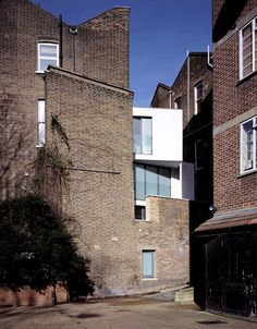 Glass-fronted family residence squashed between two terraced houses in west London, on a site less than three metres wide at the front.