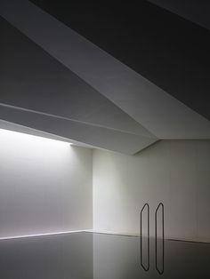 Underground Spa. Sleek minimal white indoor pool. Elegant pool ladder.
