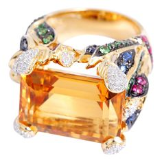 DeMesy Beautiful Large Citrine Ring with Diamonds & Colorful Stones USA  20th-21st century  This ring features a very large Yellow Citrine (apx. 15 carats) with a very ornate setting with pink, green, and blue stones. The Citrine itself is held up by little pave diamond clusters.