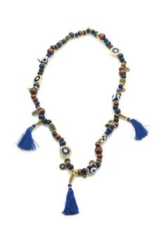 Evil eye charm, wood and glass African beads, and blue tassels with metal spacers. by Hendrikka Waage.   Perfect for the summer -- www.lastashop.com #Fashion #Jewelry #Style #Summer #Icelandic #Lastashop