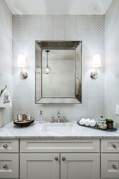 Light walls and a white vanity keep this small bathroom feeling bright and open. Patterned gray and white tile provides a lovely backdrop for the mirror and complements the light marble countertop. Elegant metallic accessories add a subtle touch of glamor.