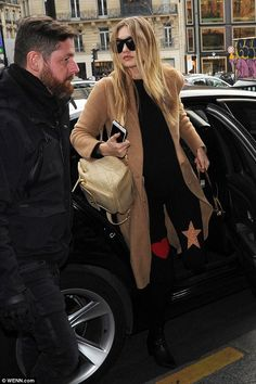Gigi Hadid wearing Karen Walker Deep Worship Sunglasses, Saint Laurent Monogram Matelasse Bag, Chanel Lambskin Quilted Backpack and Stuart Weitzman Zepher Booties