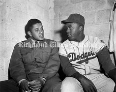 Brooklyn Dodgers star Jackie Robinson (right) talks with Dodgers pitcher Don Newcombe at Mooers Field on April 8, 1952. The Dodgers came to Richmond to play an exhibition because Newcombe was in basic training at Camp Pickett.