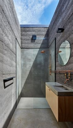 Using concrete, wood and plenty of sunlight through a skylight this shower in a retreat home is simple, minimalist and beautiful