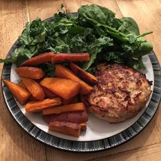 Lean turkey burger with sweet potato wedges with uncooked spinach and kale, following The Body Coach 90 Day SSS plan.