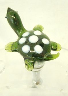 "New Hand Blown Glass Turtle Wine Stopper by LS Arts. $13.99. 4"" Tall. Blown Glass. Gift Boxed. This New Hand Blown Glass Turtle Wine Stopper measures 4 inches tall.  This adorable turtle is green with white spots on its back.    The base is graduated to fit nearly all wine bottles.  A rubber gasket surrounds the base to ensure the bottle stopper is seated securely in the wine bottle.  This Turtle Wine Stopper would make a wonderful gift for others or for yourself.  Our..."