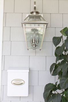 Exterior of Tori Wesszer's grey shake home white mailbox and silver wall lanterns