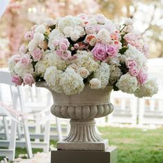 White hydrangeas and blush spray roses will fill silver urns flanking the altar.