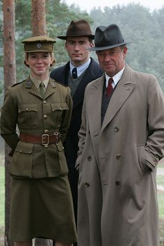 """Foyle's War- Sgt. Paul Miner (played by Anthony Howell), Sam, (Samantha Stewart, played by Honeysuckle Weeks), and Detective Chief Superintendent Christopher Foyle, (Michael Kitchen). """"1940: Britain stands alone against the might of Nazi Germany. DCS Foyle, Hastings Police, confronts the darkest acts of humanity on a daily basis, investigating murder, looting, and theft."""""""