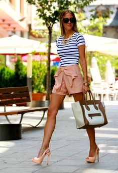 The woman is wearing a striped short-sleeved T-shirt. The stripeds of T-shirt are blue and white. She wears a pink short trourses and a pink high-heeled shoes. The woman wear a brown and white handbag.