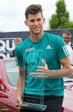 Austria's Dominic Thiem holds the trophy during the victory ceremony after winning the ATP Mercedes Cup tennis tournament in Stuttgart, southwestern Germany, on June 13, 2016. Thiem won the final against Germany's Philipp Kohlschreiber. / AFP / THOMAS