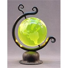 Czech vaseline world globe paperweight.  Made in the Bohemian region of the Czech Republic from the finest quality yellow vaseline glass, the globe sits in a black cast frame and actually spins as a real globe would.